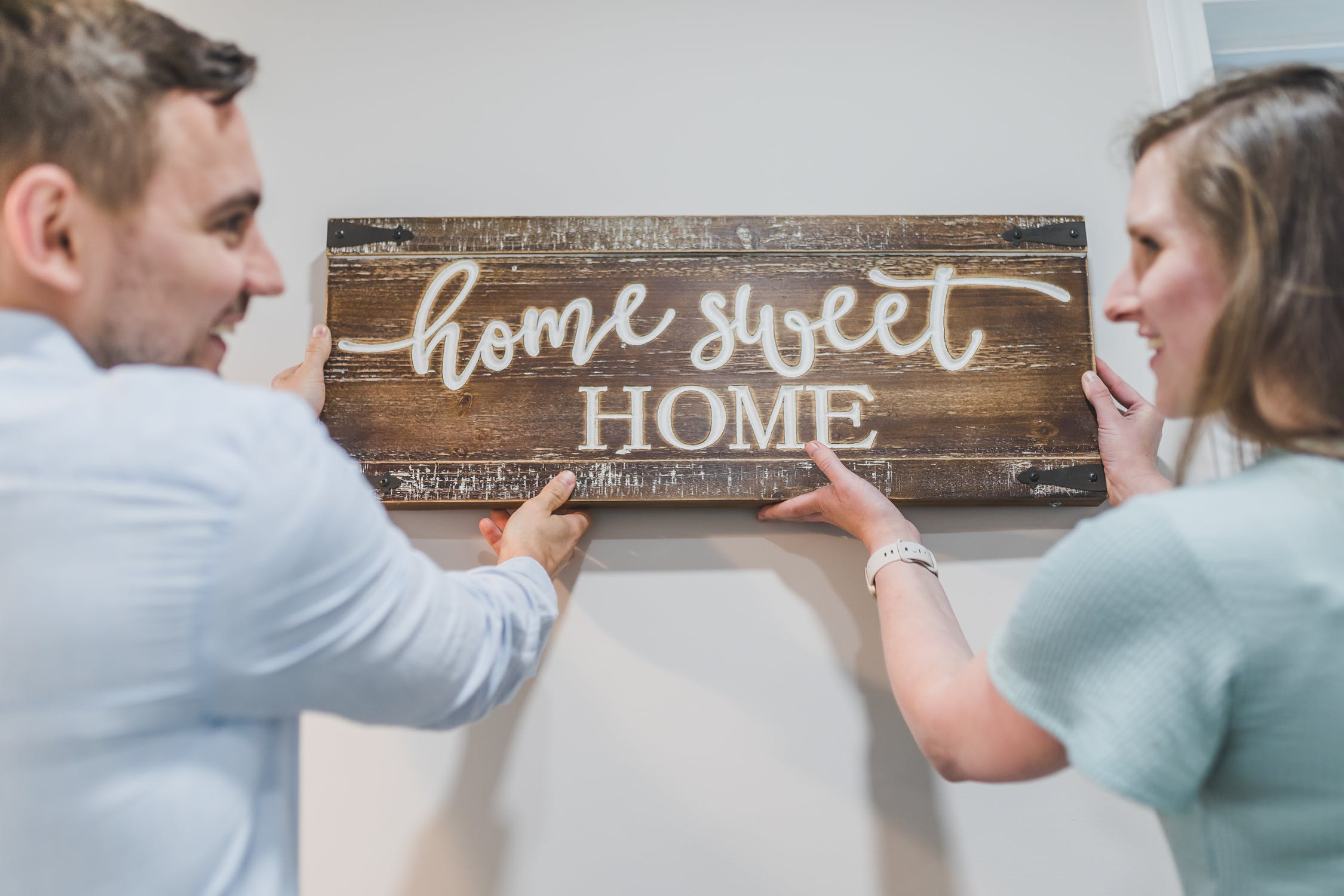 Couple holding home sweet home sign